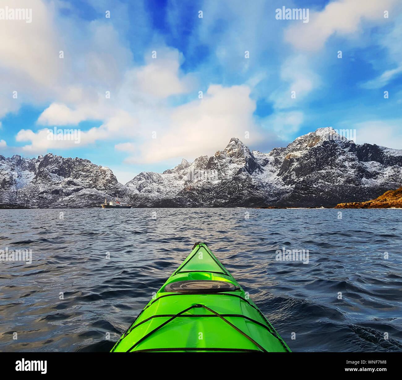 Kayak en bahía verde pequeño fiordo en las Islas Lofoten rodeado de montañas nevadas y cielo azul. Noruega Foto de stock