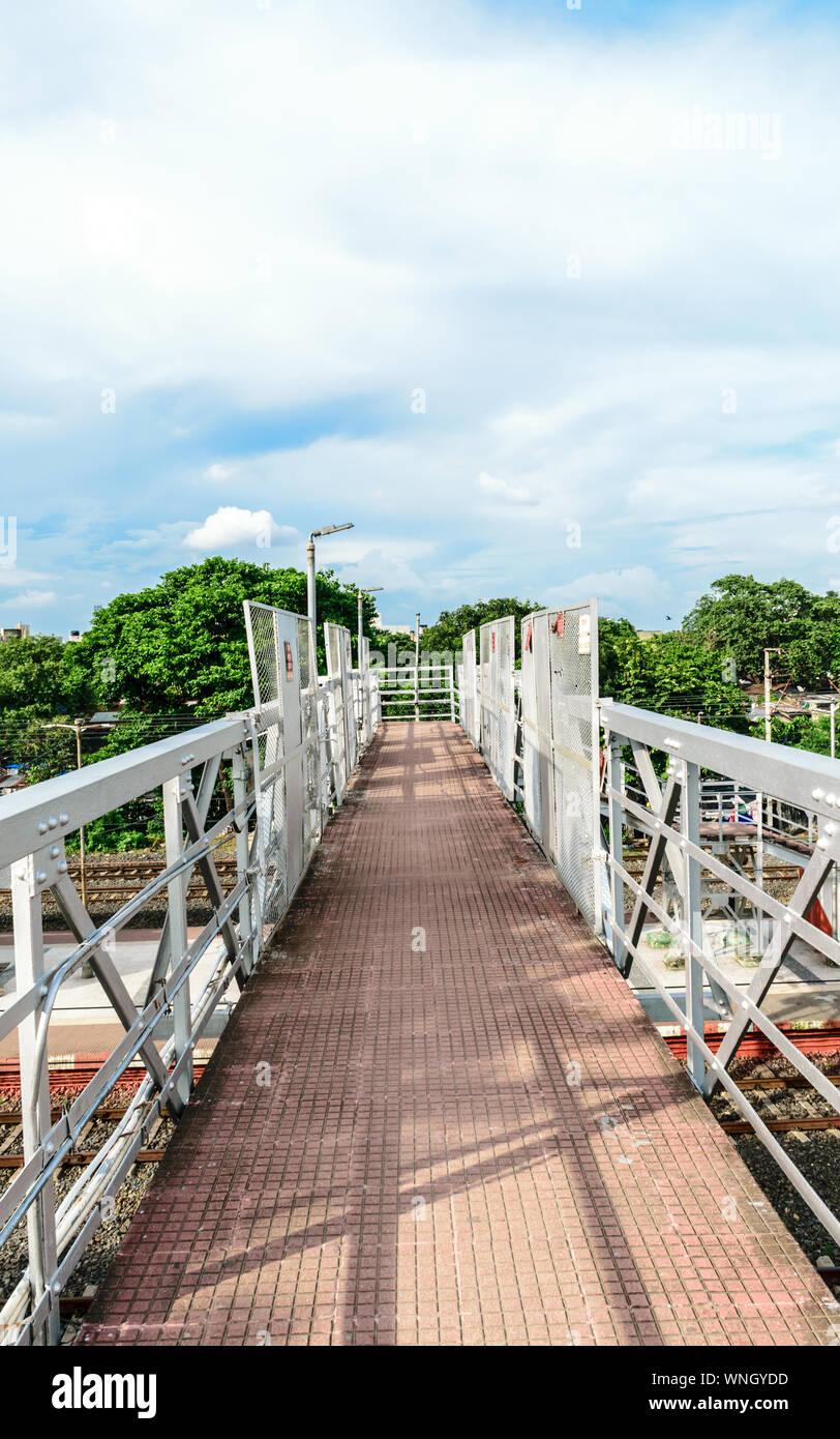 Pie sobre el puente de ferrocarril o simplemente llama a través de un puente en una estación de ferrocarril casi completa de la plataforma para que los pasajeros puedan pasar a través de una estación de tren p Foto de stock