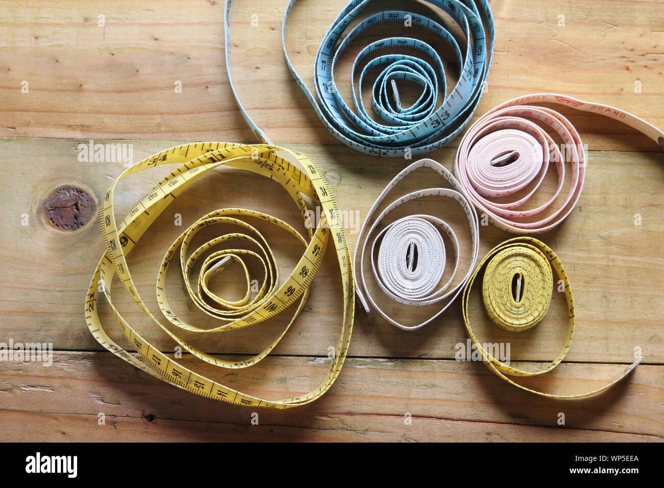 Las medidas de longitud de cinta sobre fondo de madera Foto de stock