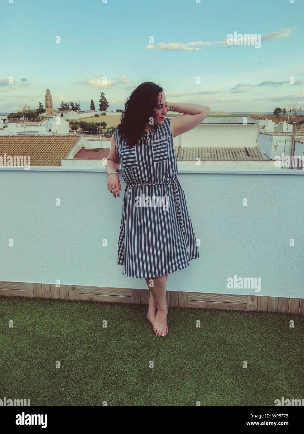 Mujer relajado en un traje a rayas y descalzo sobre el césped de la terraza Foto de stock