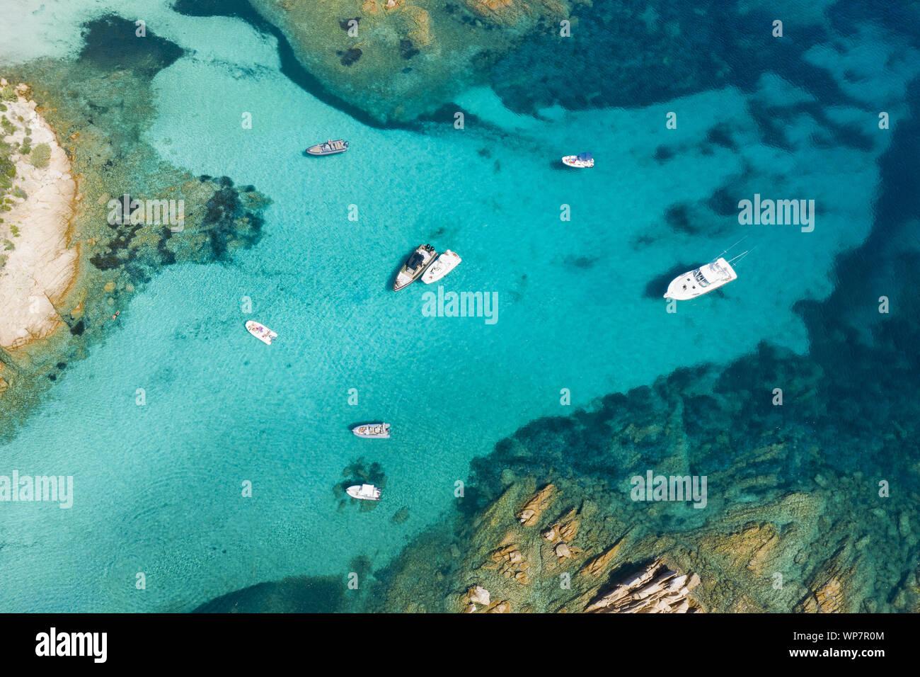 Vista desde arriba, la impresionante vista aérea de algunos barcos y yates de lujo flotando sobre un agua de color turquesa. Parque Nacional Archipiélago de Maddalena, en Cerdeña. Foto de stock