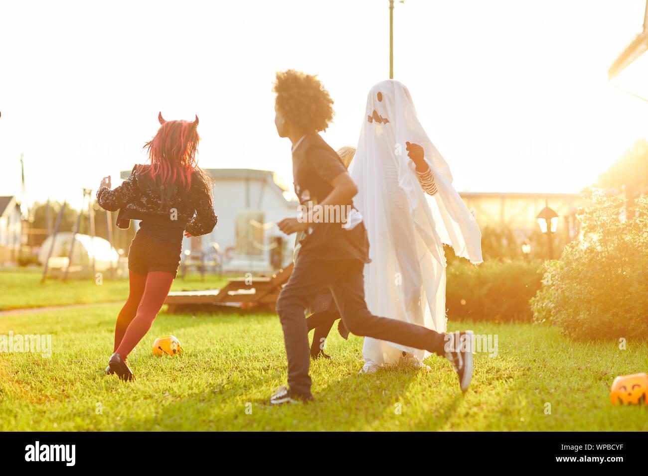 Grupo multiétnico de niños disfrazados corriendo en el césped mientras se divierten en Halloween y jugar con la luz del sol, espacio de copia Foto de stock