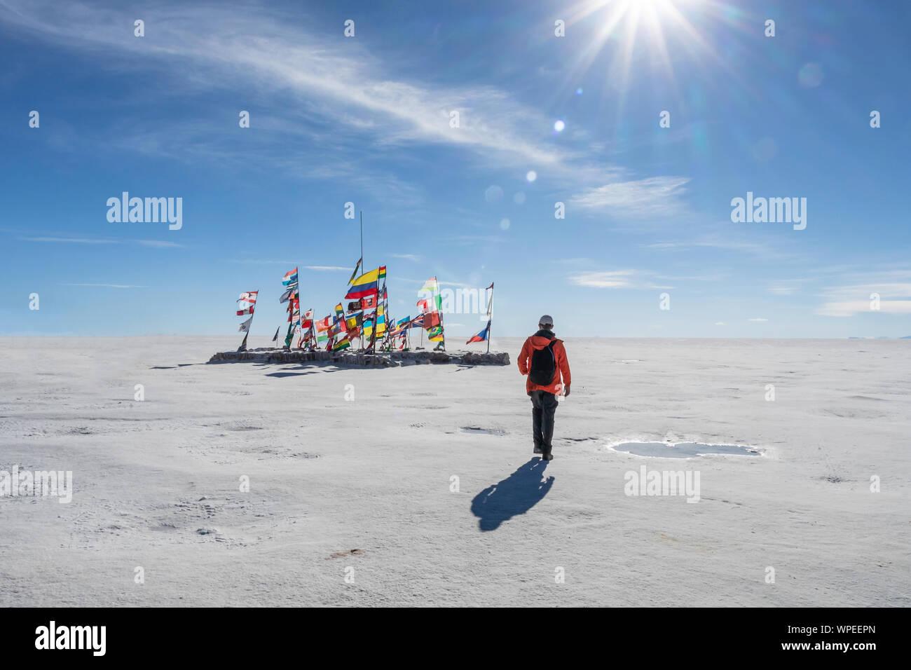 Joven caminando hacia las banderas internacionales de diferentes países en el Salar de Uyuni en día soleado con rayos de sol, Bolivia, South America Travel voc Foto de stock