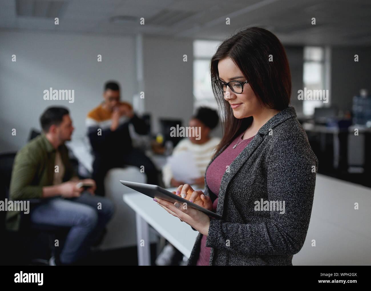 Feliz joven empresaria mediante tableta digital en la oficina y sus colegas discutiendo en segundo plano. Foto de stock