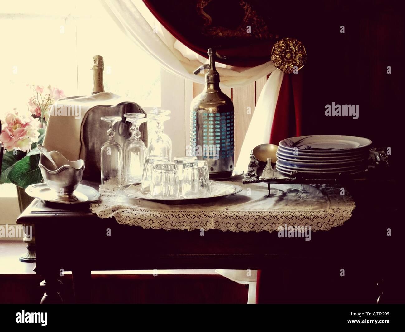 Platos y vasos en la mesa en casa Foto de stock