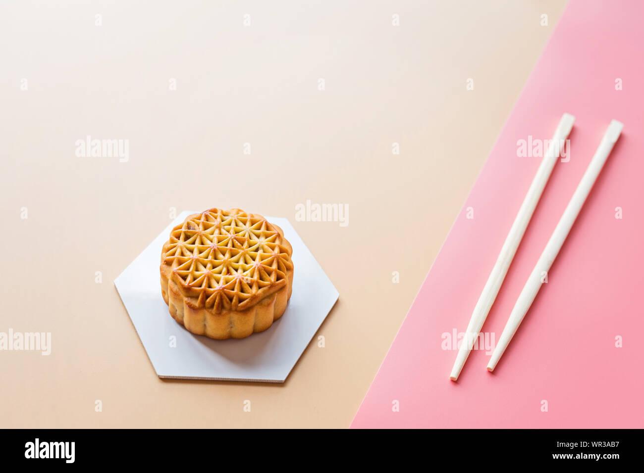 Plano de laicos Festival Chino, mediados de otoño Festival de postre torta de luna sobre fondo de colores con palillos. Vista superior, copia el espacio, Boceto, sobrecarga Foto de stock