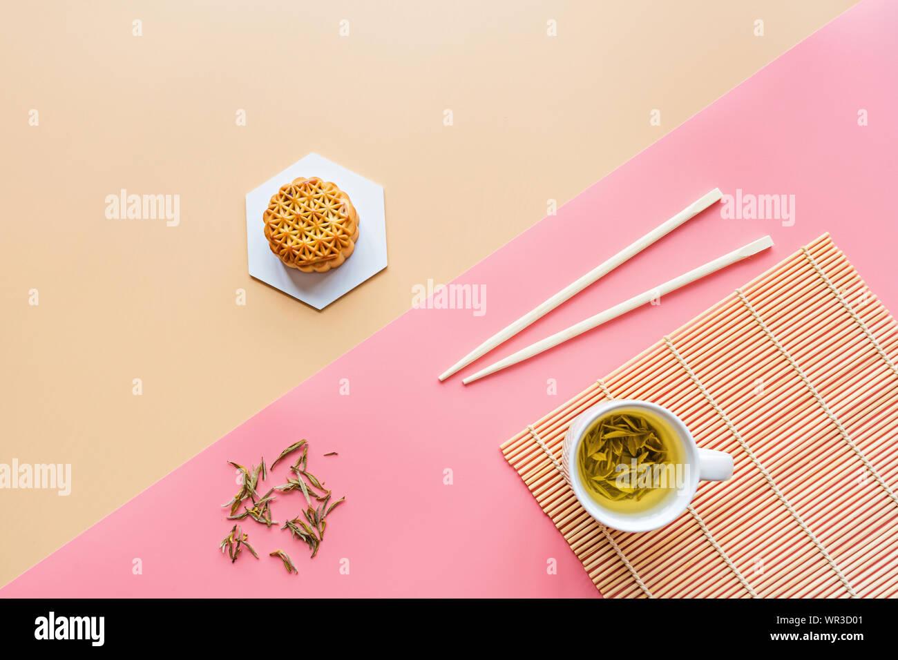 Plano de laicos Festival Chino, mediados de otoño Festival de postre torta de luna sobre fondo de colores con té verde y palillos. Vista superior, copia el espacio, Boceto Foto de stock