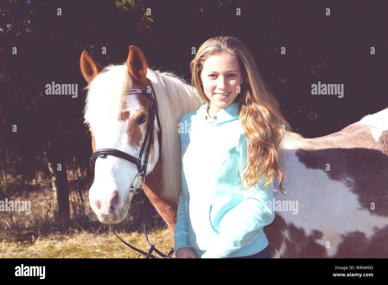 Retrato de mujer sonriente a caballo en campo permanente Foto de stock