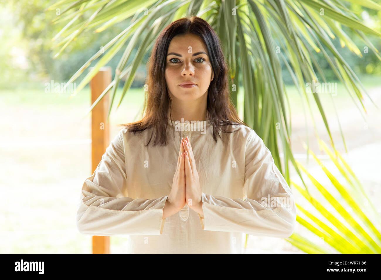 Mujer morena medita sobre la naturaleza de fondo. Ejercicios de yoga en el retiro. Foto de stock