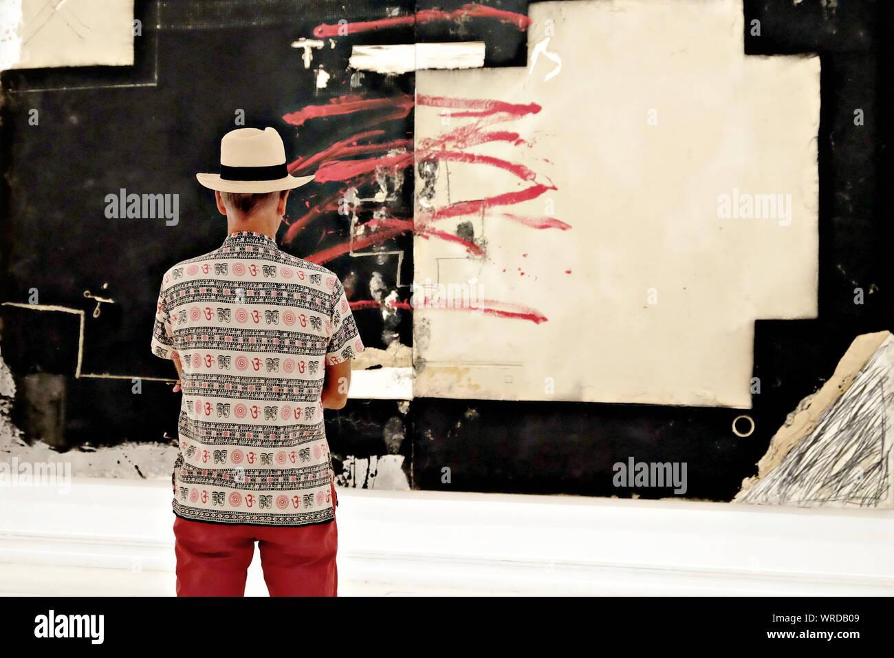 Visitante busca una pintura abstracta con los mismos colores de su ropa Foto de stock