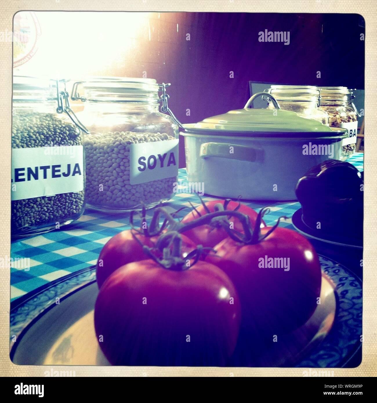 Los tomates frescos por frascos de soja y lentejas verdes en la mesa Foto de stock