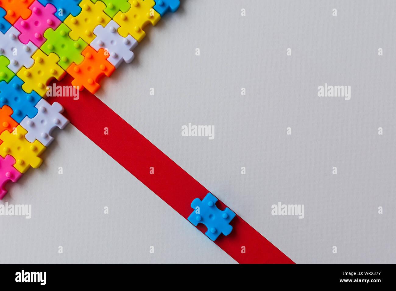 Puzzle de plástico de colores sobre papel blanco de fondo, falta un rompecabezas en línea roja para completar con copia espacio, estrategia empresarial trabajo en equipo Foto de stock