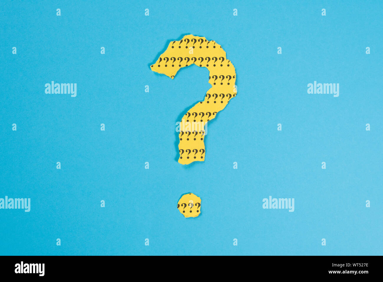 Símbolo de interrogación desde un teared papel amarillo sobre fondo azul. Concepto de FAQ, Preguntas y respuestas, preguntas y riddle Foto de stock