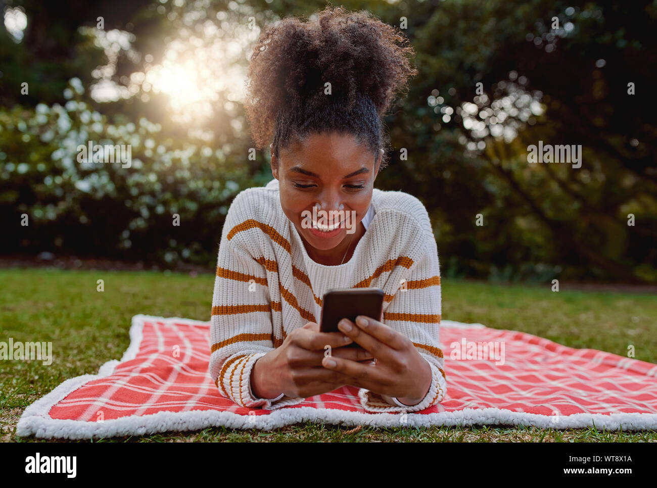 Relajado sonriente joven afroamericana acostado sobre una manta sobre el césped en el parque a través de teléfono móvil - Estudiante en su móvil en College Park Foto de stock