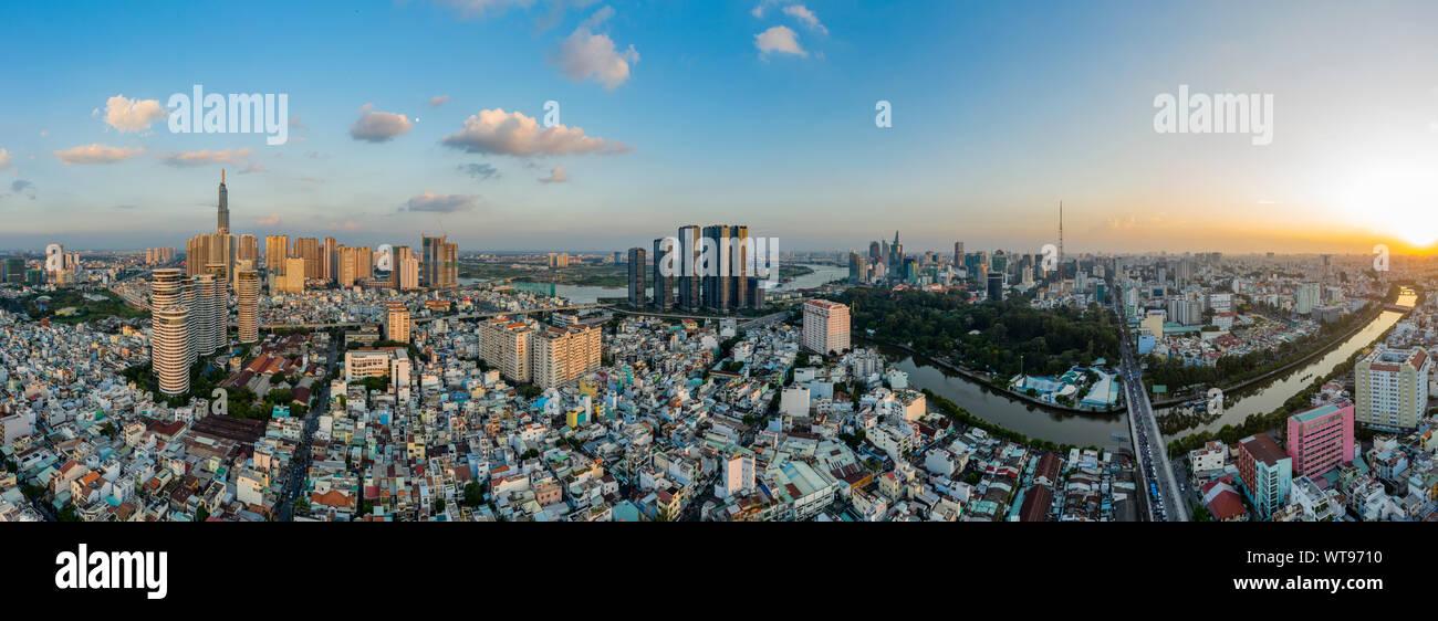Ultra alta resolución antena dramático panorama de Binh Thanh district Ho Chi Minh tomando en los principales edificios de la ciudad y enfrente del río al atardecer Foto de stock