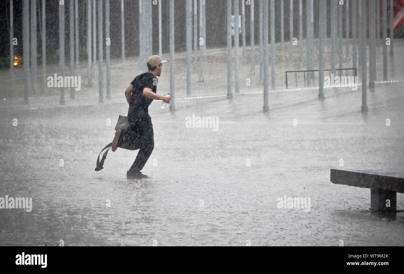 Hombre corriendo en la lluvia en la calle en la ciudad Foto de stock