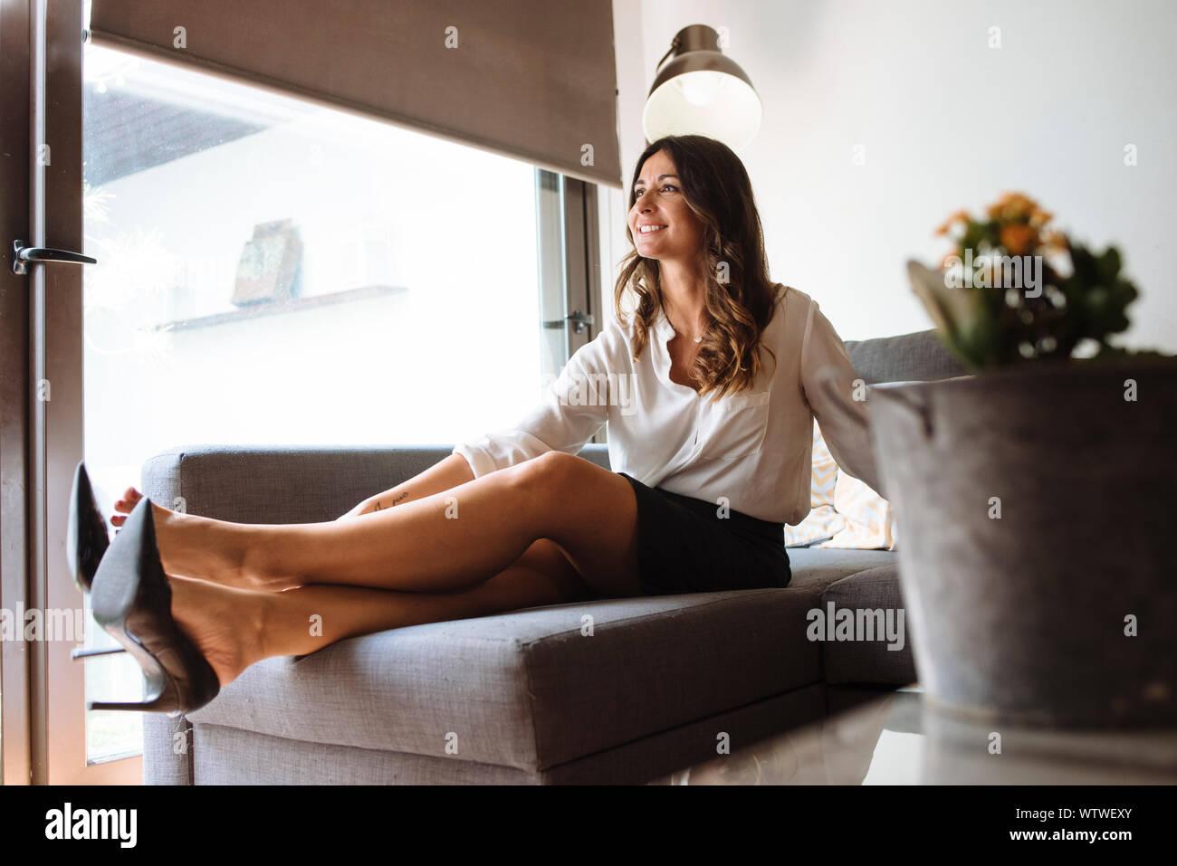 Mujer morena con ropa de oficina de despegar sus zapatos en un sofá. Foto de stock