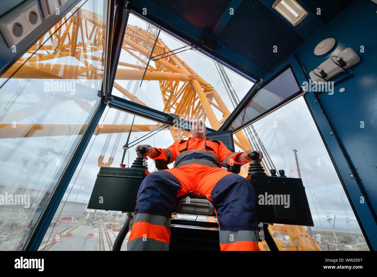 Gruista Martin Redmond dentro de su cabina a bordo del 'Big Carl', la grúa más grande del mundo, que se está preparando para comenzar a trabajar en Hinkley Point C Power Station en Somerset. Capaz de soportar hasta 250 m de altura, la grúa Sarens SCC-250 puede alcanzar mayor que la torre más alta en la London's Canary Wharf y puede transportar 5.000 toneladas en un solo elevador. Foto de stock