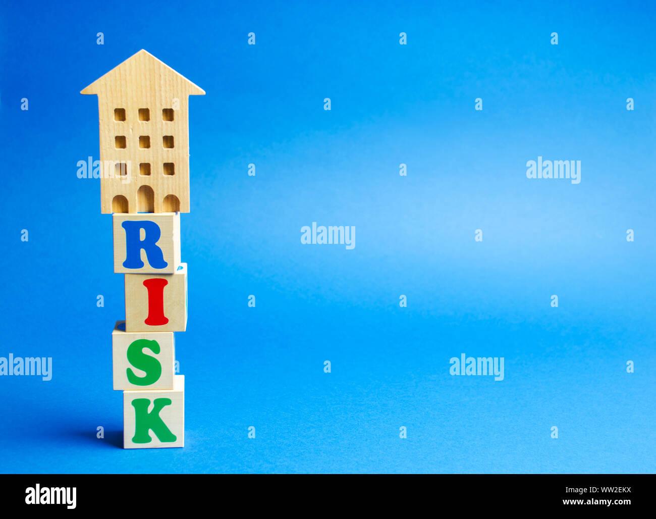Bloques de madera con la palabra riesgo y una casa en miniatura. Riesgo de inversión inmobiliaria. Las inversiones arriesgadas. Pérdida de la propiedad por falta de pago. Las deudas. Mortg Foto de stock