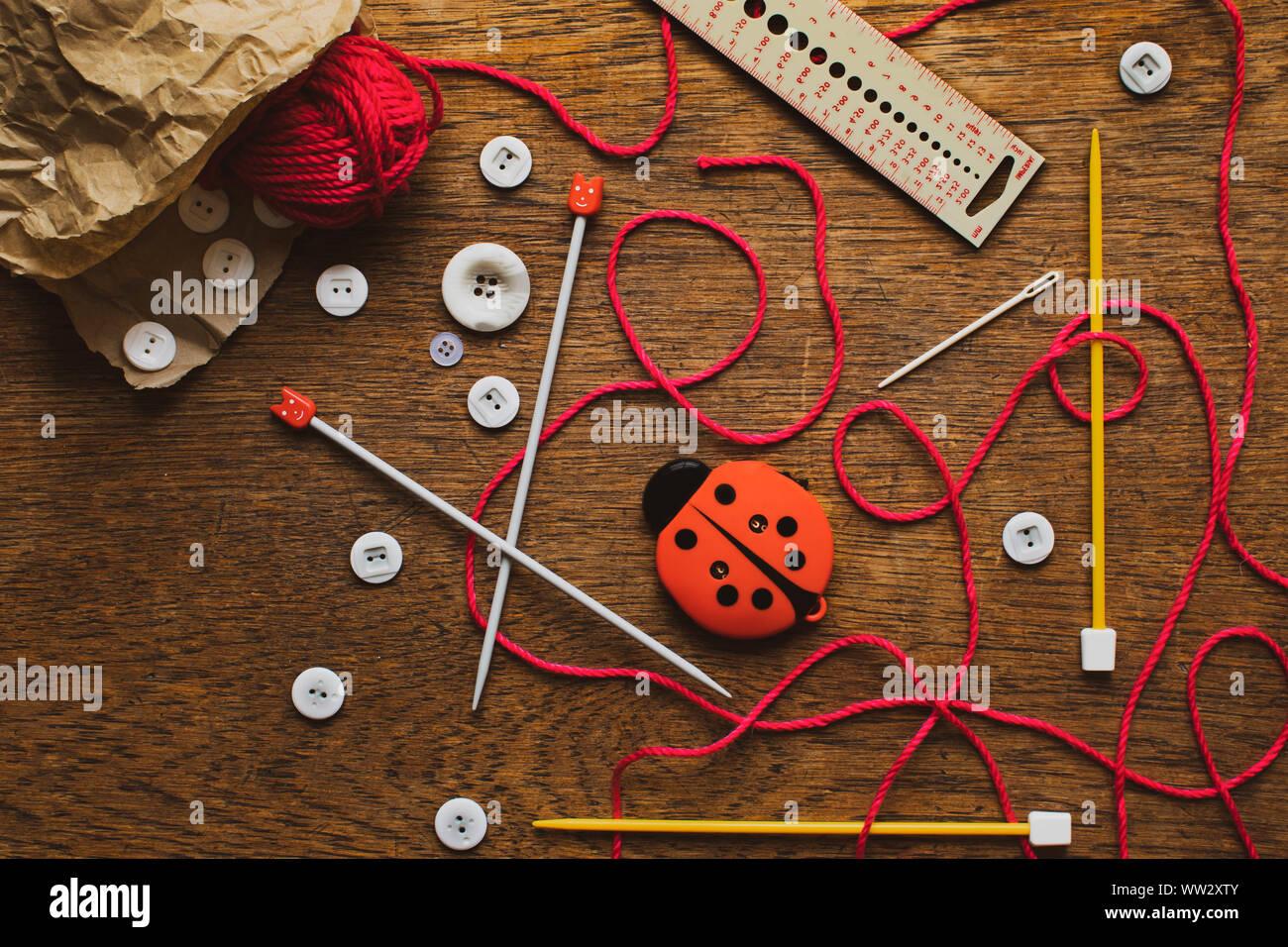 Herramientas y accesorios tejer derramándose desde una bolsa de papel marrón en una mesa de madera arriba Foto de stock