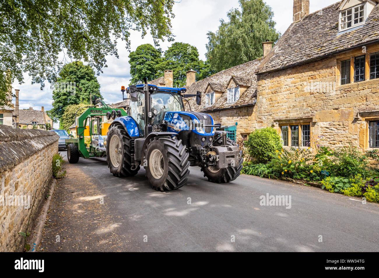 Maquinaria agrícola pesada la negociación de una calle estrecha en la aldea de Cotswold Snowshill, Gloucestershire, Reino Unido Foto de stock