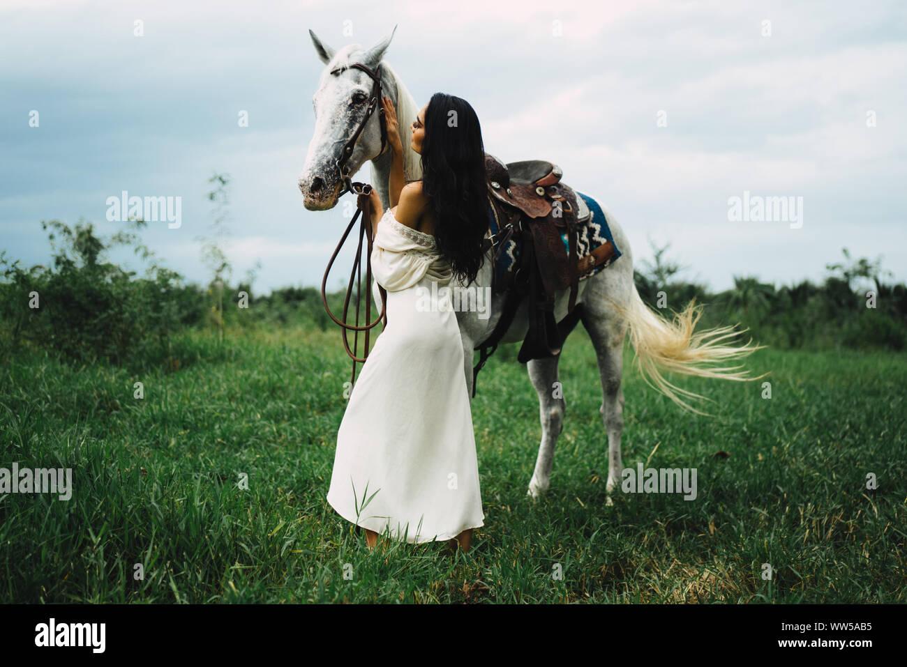 Mujer de pie junto a su caballo, Tailandia Foto de stock