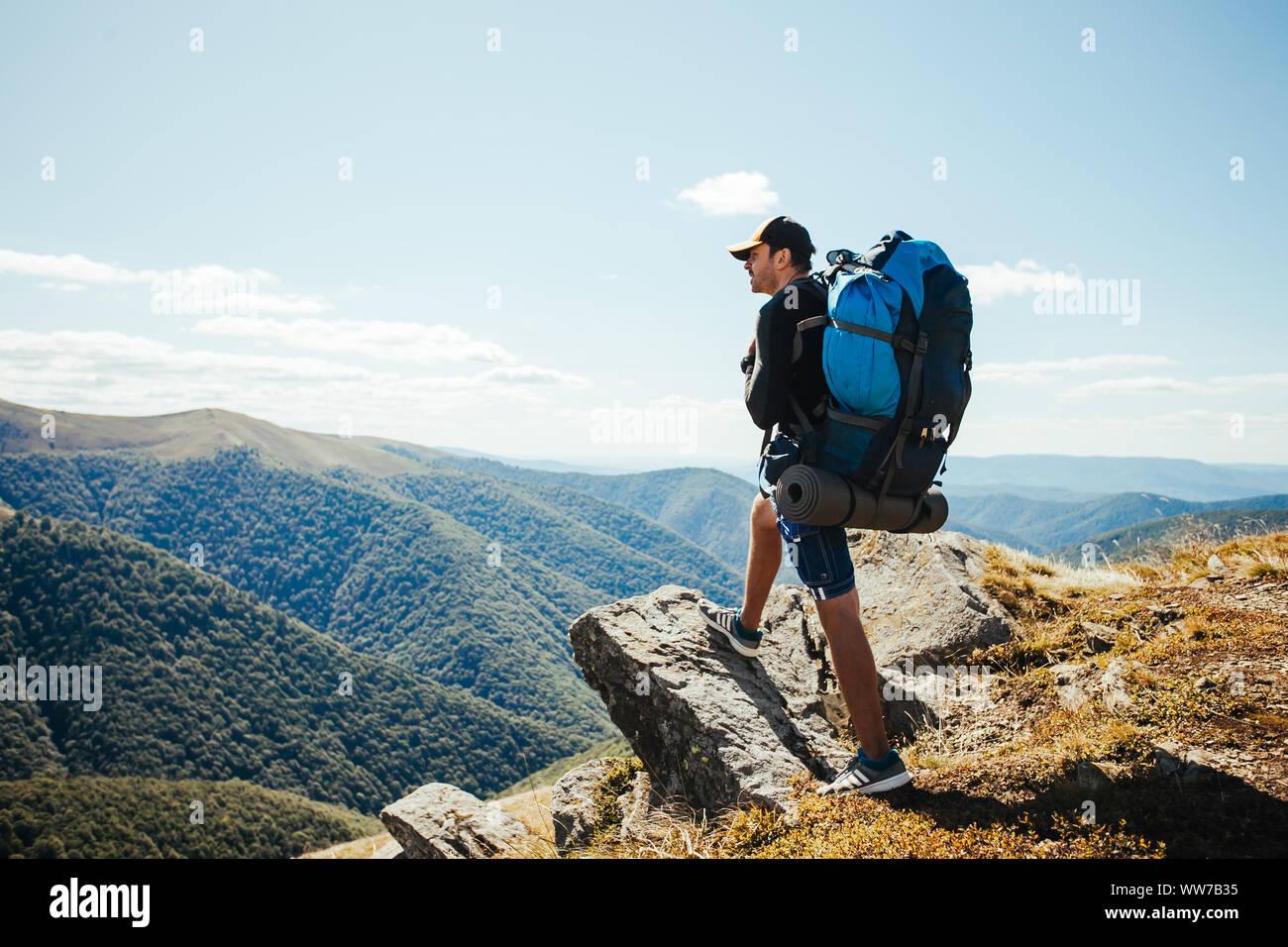 Joven con mochila de pie en la cima de la montaña Foto de stock