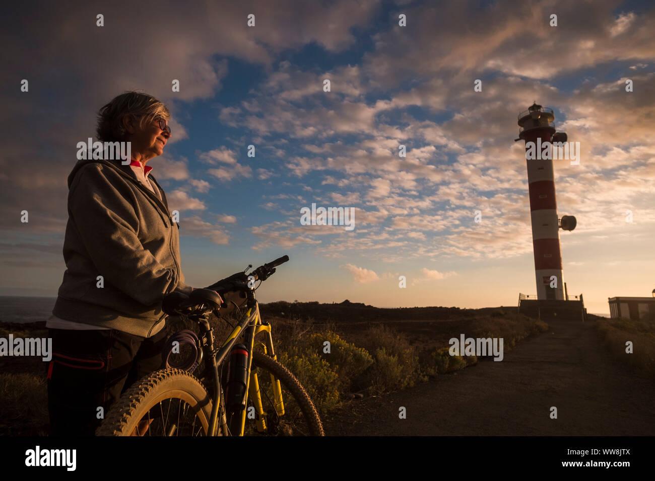 Adult Senior hermosa mujer caucásica biker de pie y disfrutar de la puesta del sol cerca de la costa y el océano. bicicletas de montaña deporte. faro en el backgorund y asombrosos colores escénica Foto de stock