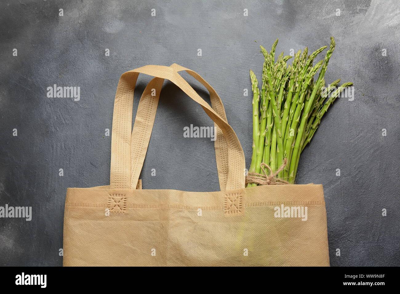 Bolsa de productos textiles reutilizables sin residuos llena de espárragos verdes y perejil Foto de stock