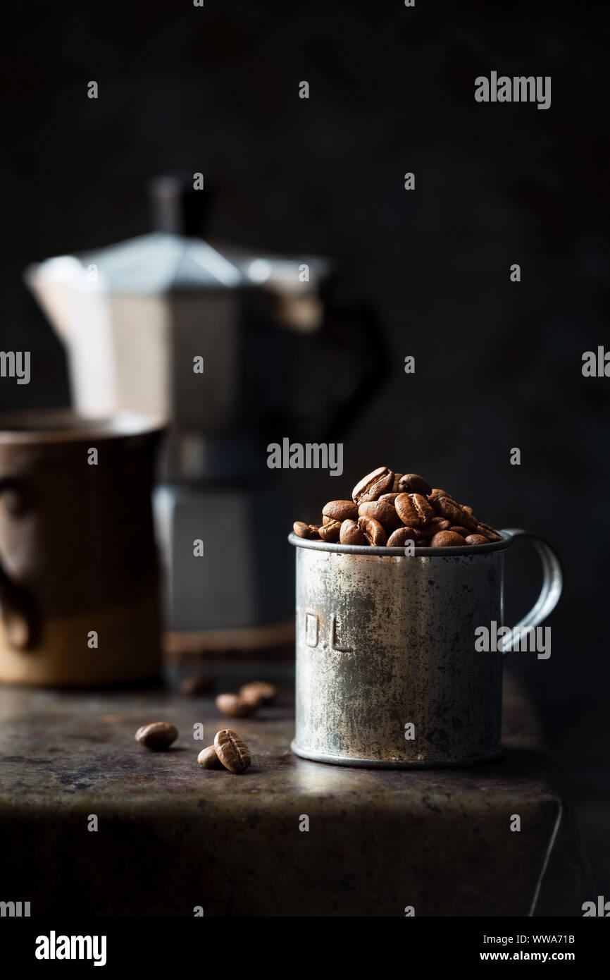 Los granos de café en una taza medidora de estaño contra el oscuro fondo rústico. Low Key con poca profundidad de campo. Foto de stock
