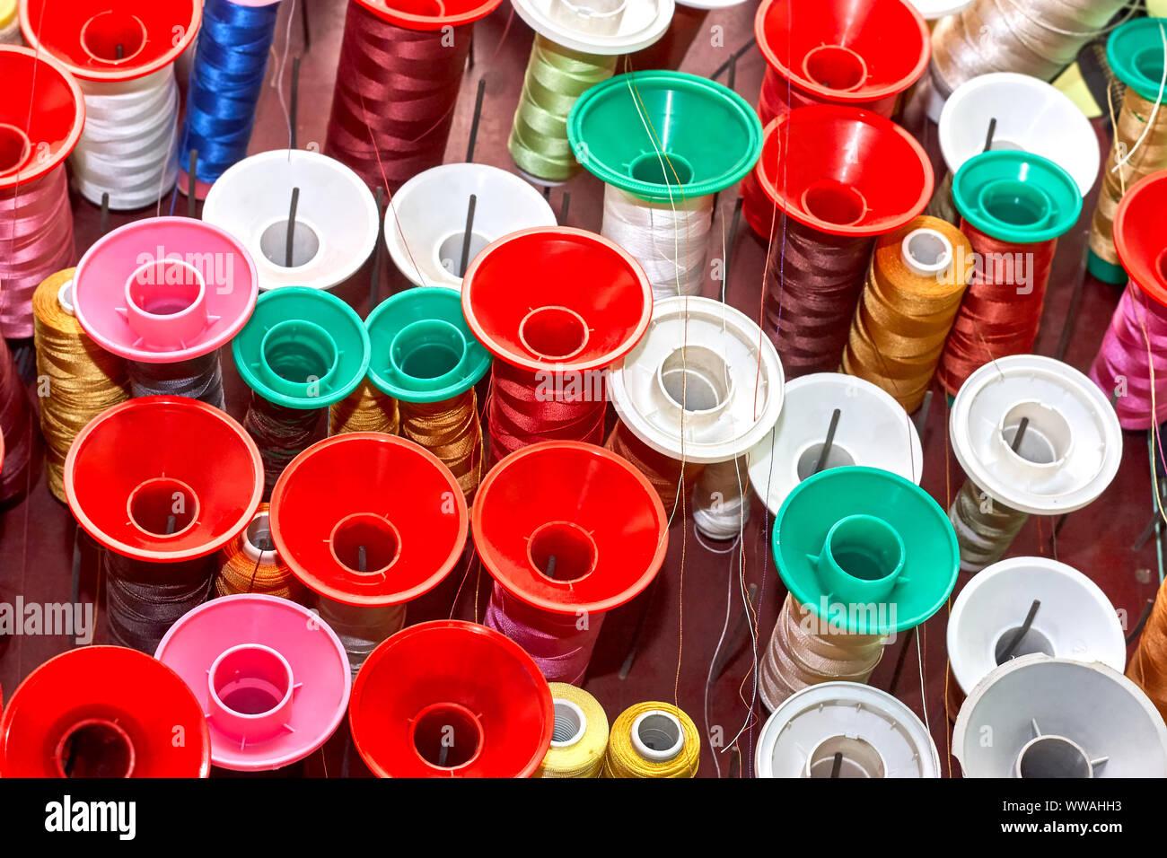 Carretes de hilo de colores en un taller de costura Foto de stock