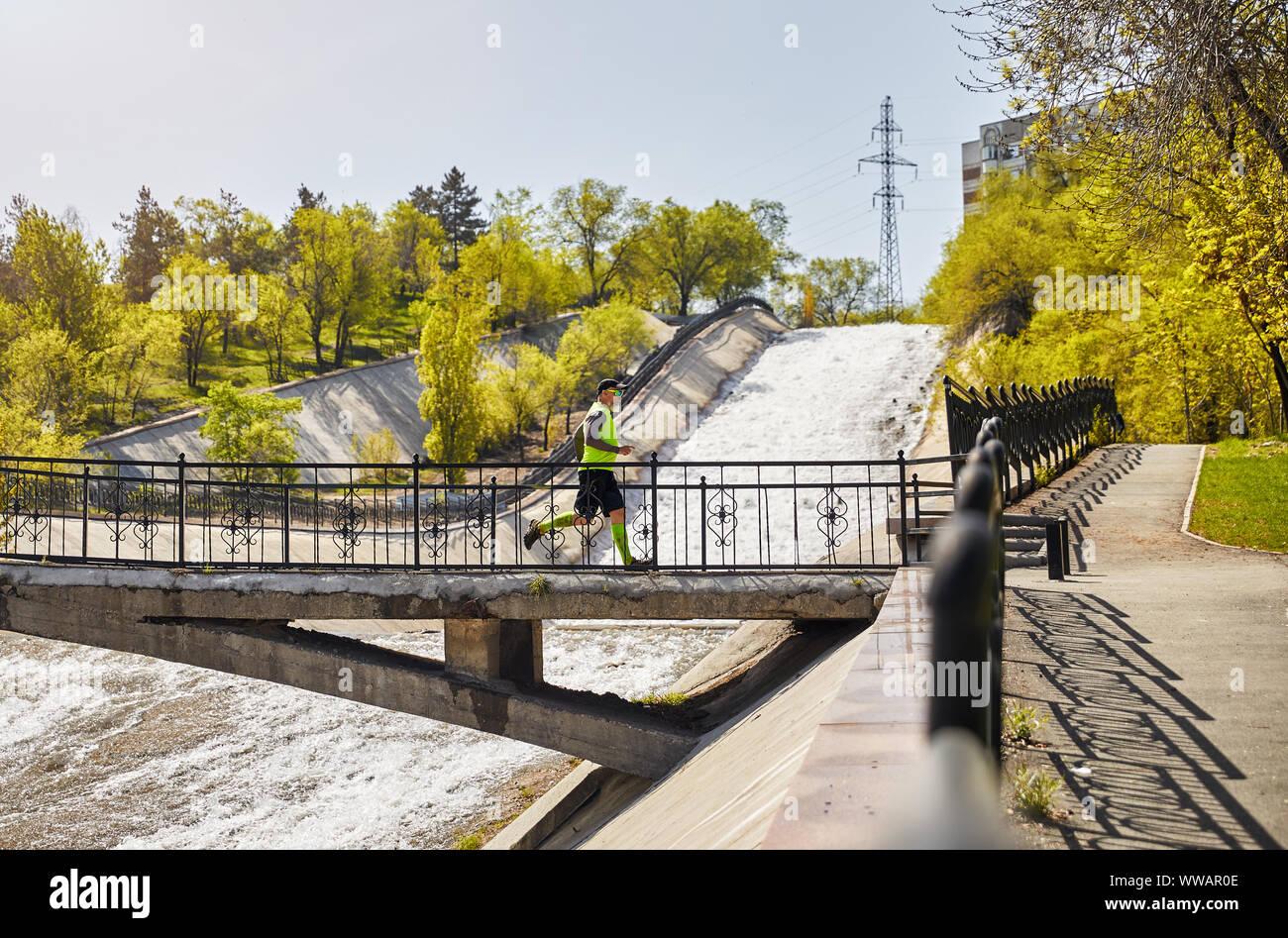 Hombre con barba gris que se ejecutan en el puente que cruza el río en la mañana. Concepto de estilo de vida saludable Foto de stock