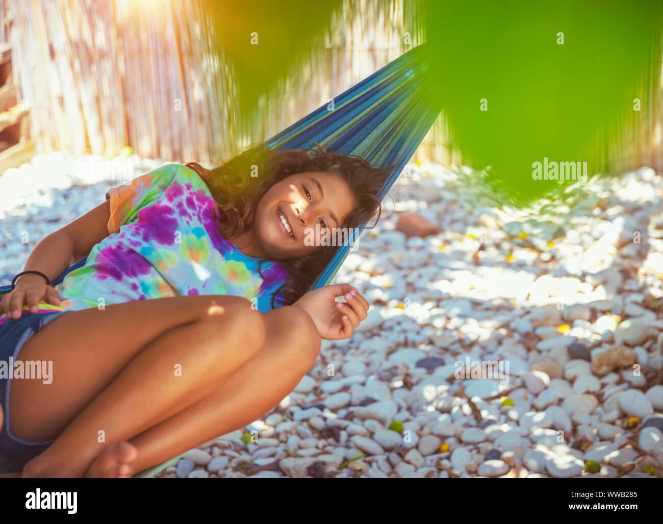 Retrato de una niña descansando en una hamaca en la playa, con placer pasar tiempo en un campamento de verano cerca del mar, disfrutando felices vacaciones activas Foto de stock