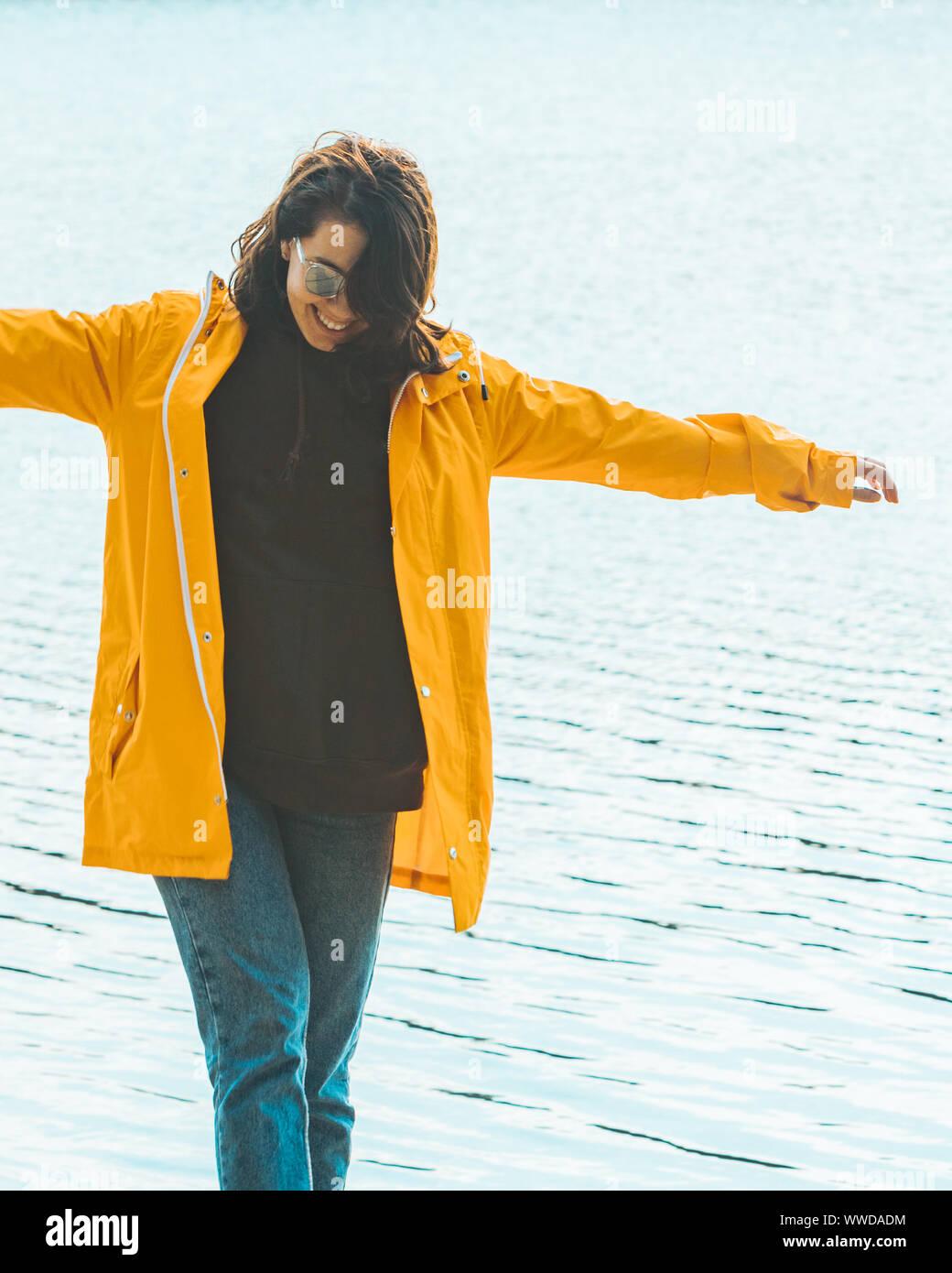 Mujer joven en amarillo impermeable en la parte delantera del agua Foto de stock