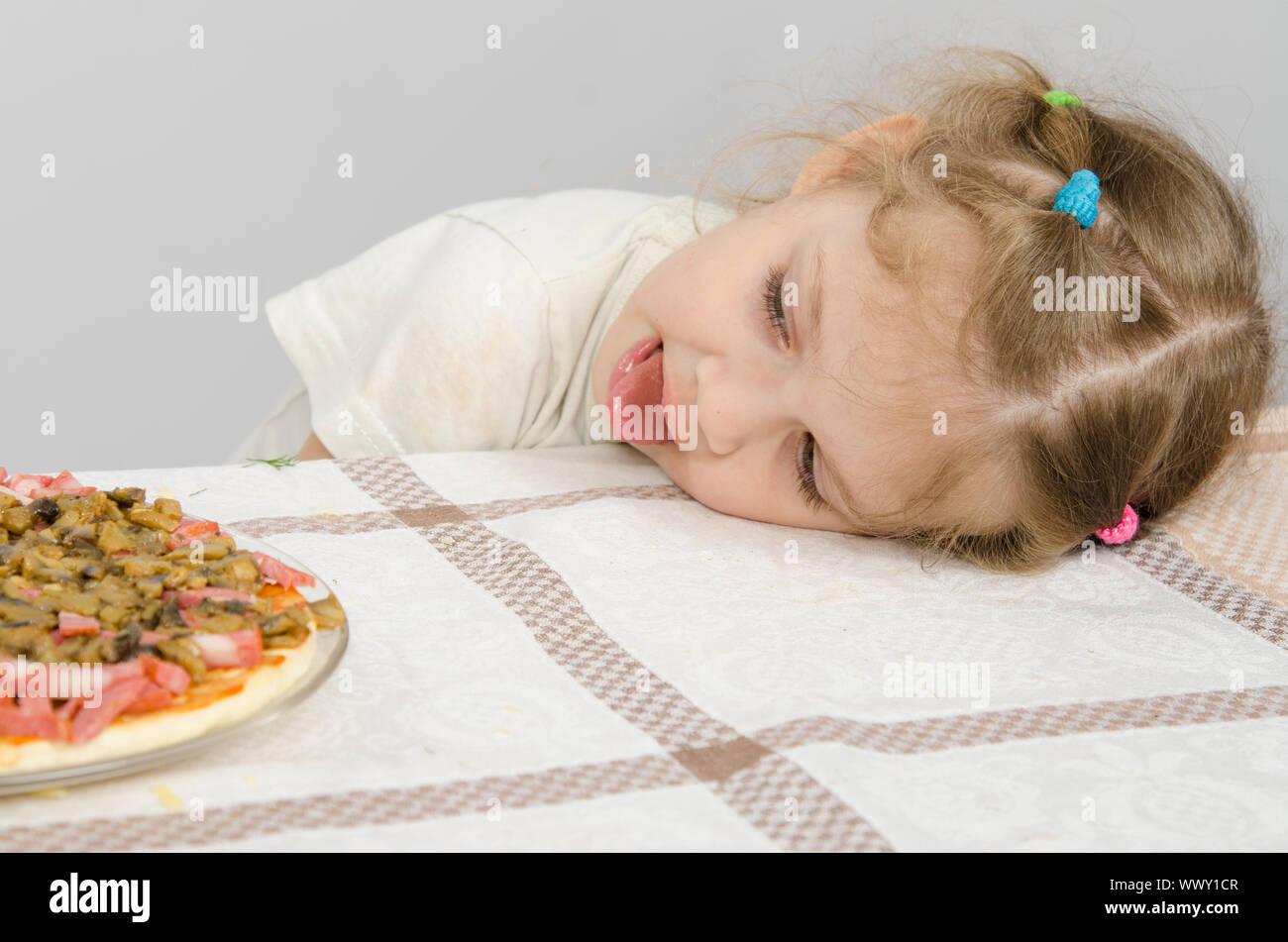 Niña con lengua protuberante descansaba su cabeza sobre la mesa y mira la pizza Foto de stock