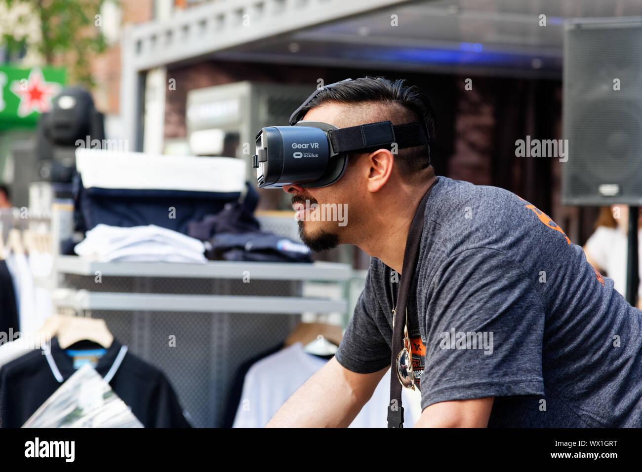 Un hombre que llevaba gafas de realidad virtual y que se movilizaban en una motocicleta simulator Foto de stock
