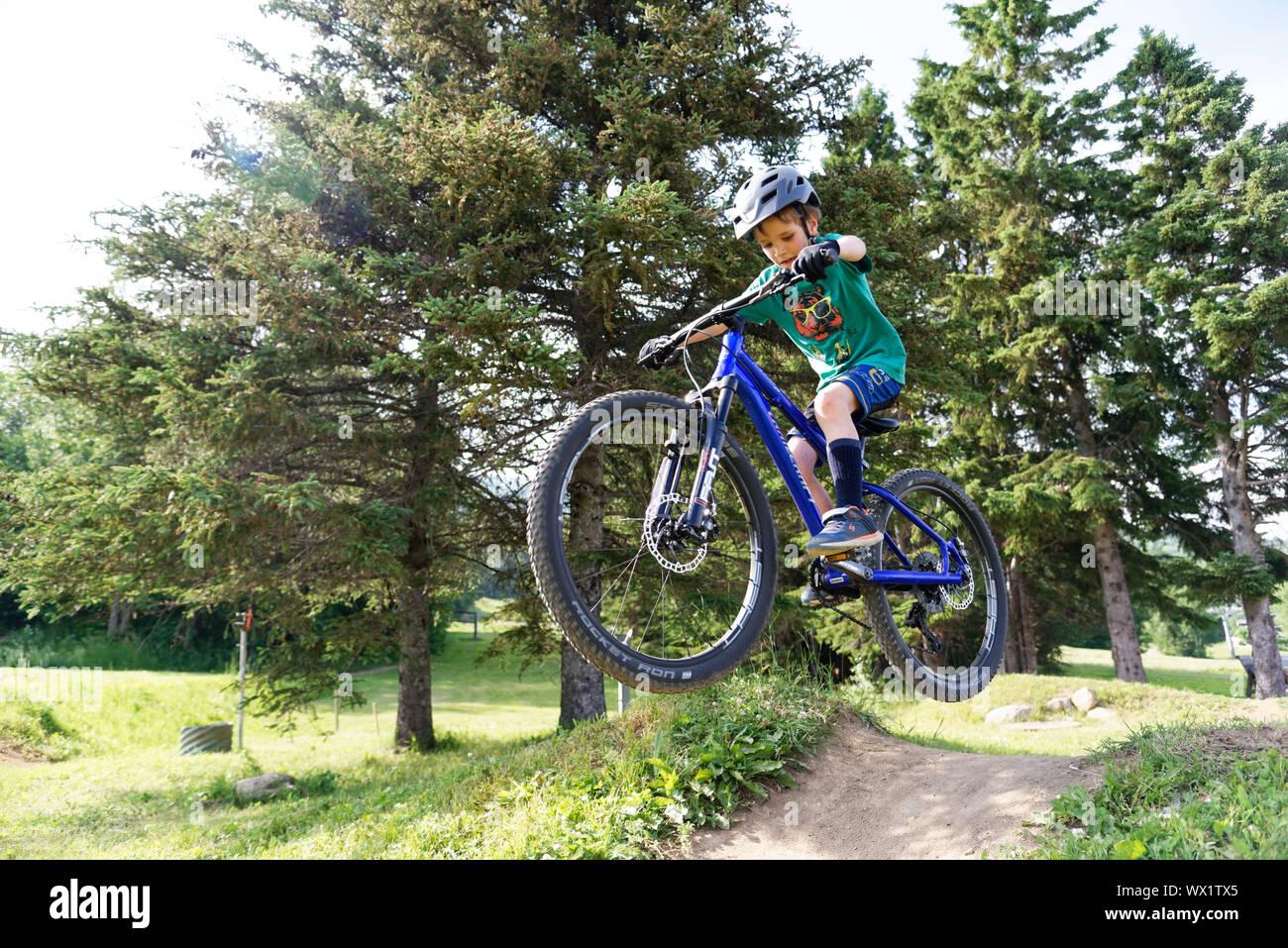 Un niño de siete años haciendo salta sobre su bicicleta de montaña Foto de stock