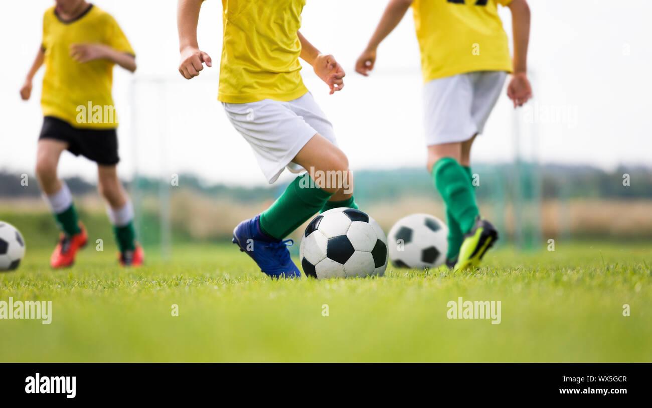 Campamento de fútbol para niños. Niños practican el regate en un campo. Los jugadores de fútbol de desarrollar buenas habilidades para el regate. Los niños en camisas amarillas formación con bolas. Foto de stock