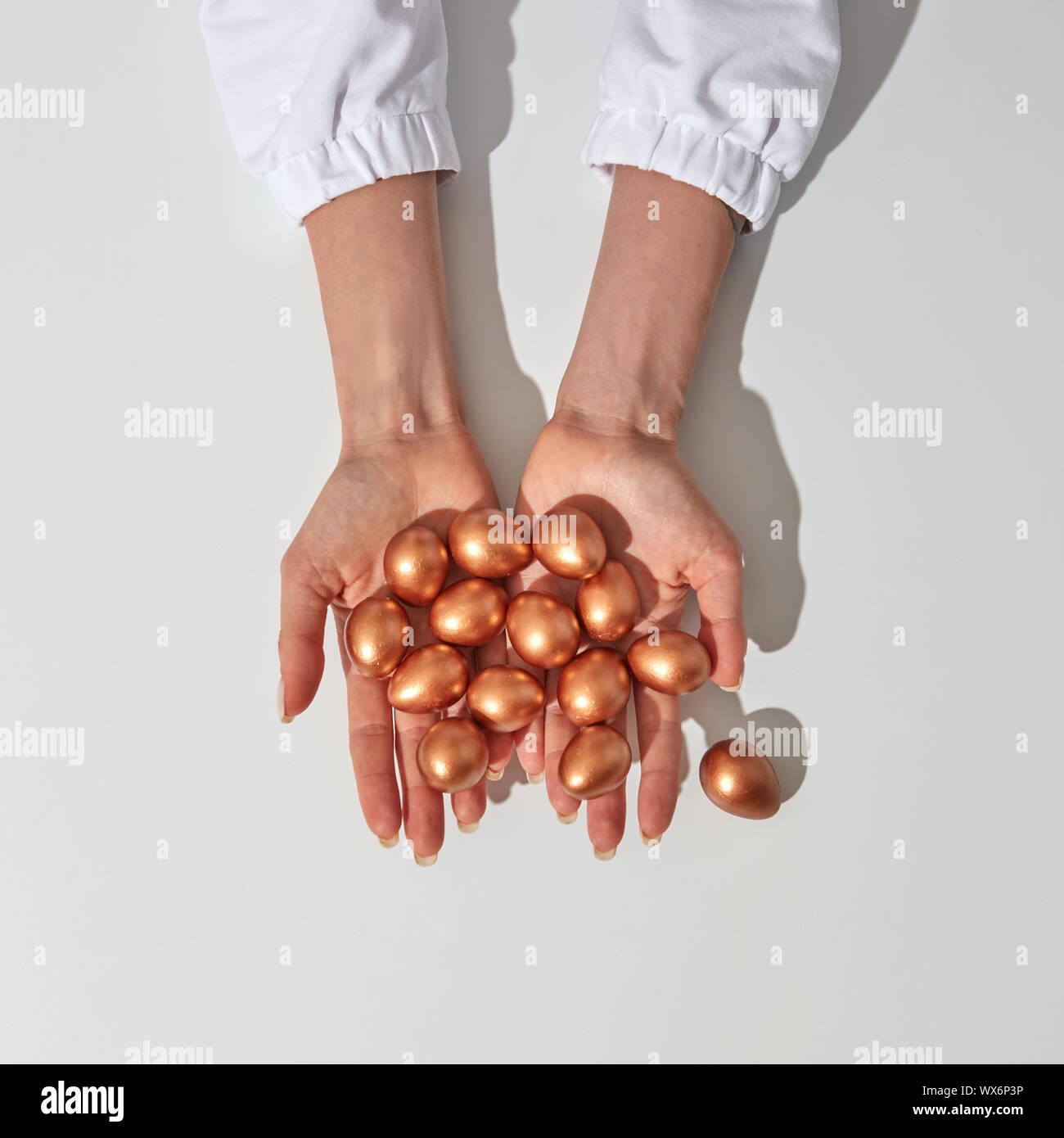 Las manos de la niña mantenga huevos pintados de oro como símbolo de la riqueza y el lucro. Alrededor del fondo gris con espacio para el texto. Foto de stock