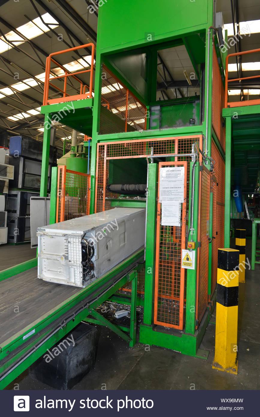 Utiliza nevera colocados en una escalera mecánica y transportados a desmontarse para su reciclaje, dentro de una planta de reciclaje Foto de stock