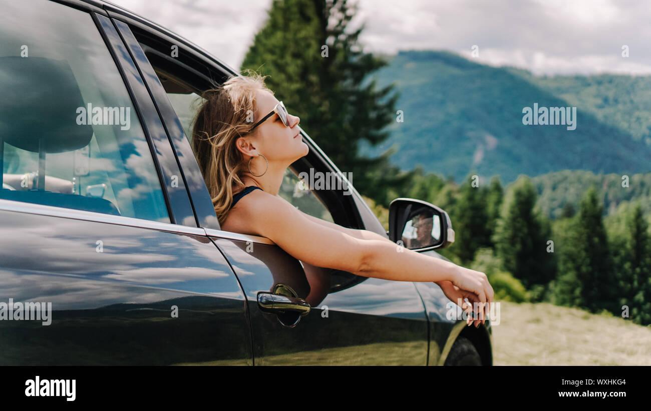 Feliz mujer viaja en coche por las montañas. Concepto de vacaciones de verano. Mujer afuera de la ventana disfrutando de Mountain View Foto de stock