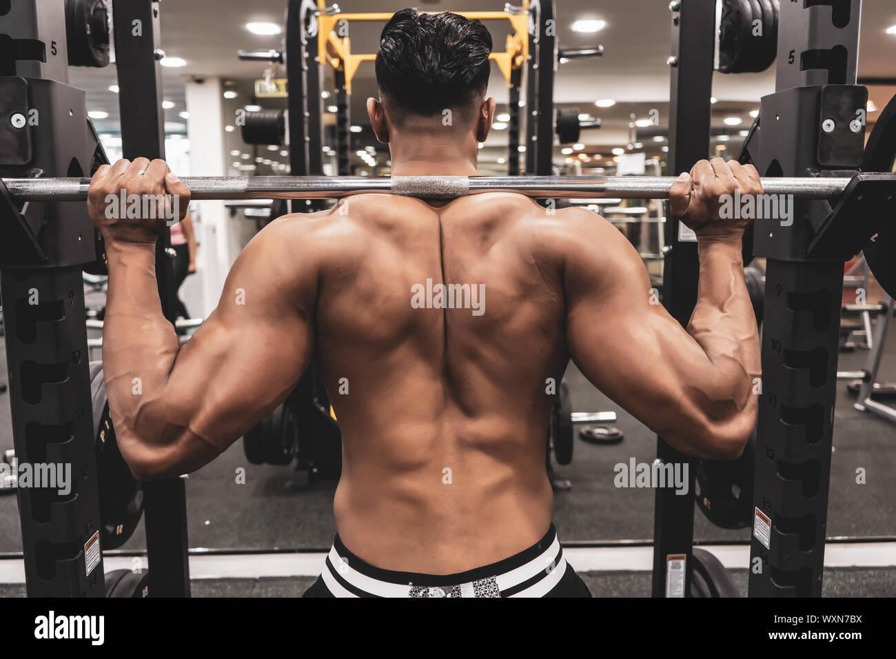 El hombre en el gimnasio. Ejecutar el ejercicio en cuclillas con el peso, en el gimnasio Foto de stock