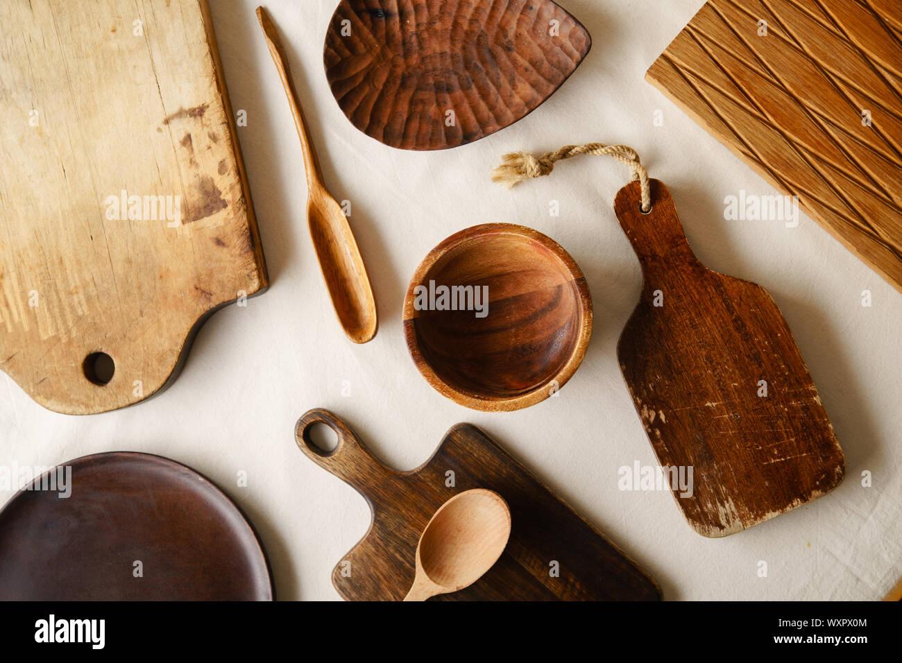 Varios las vajillas de madera. Las tablas de cortar, cucharas de diferentes formas, el plato y el cuenco en el mantel de lino Foto de stock