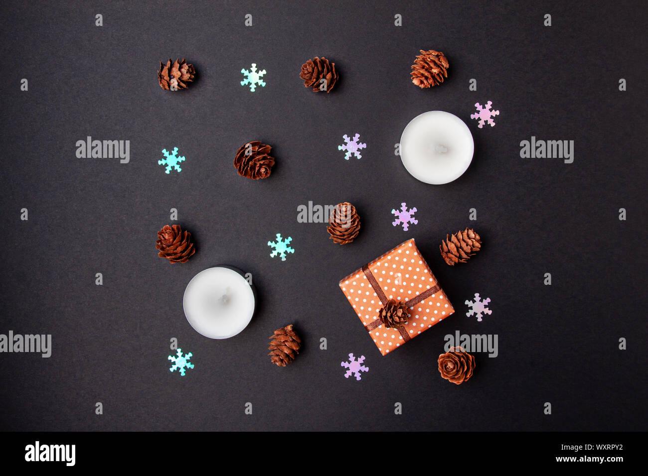 Vista superior de la geometría plana navidad laicos composición de los conos de pino, velas, falsos los copos de nieve y una pequeña caja de regalo sobre fondo negro Foto de stock