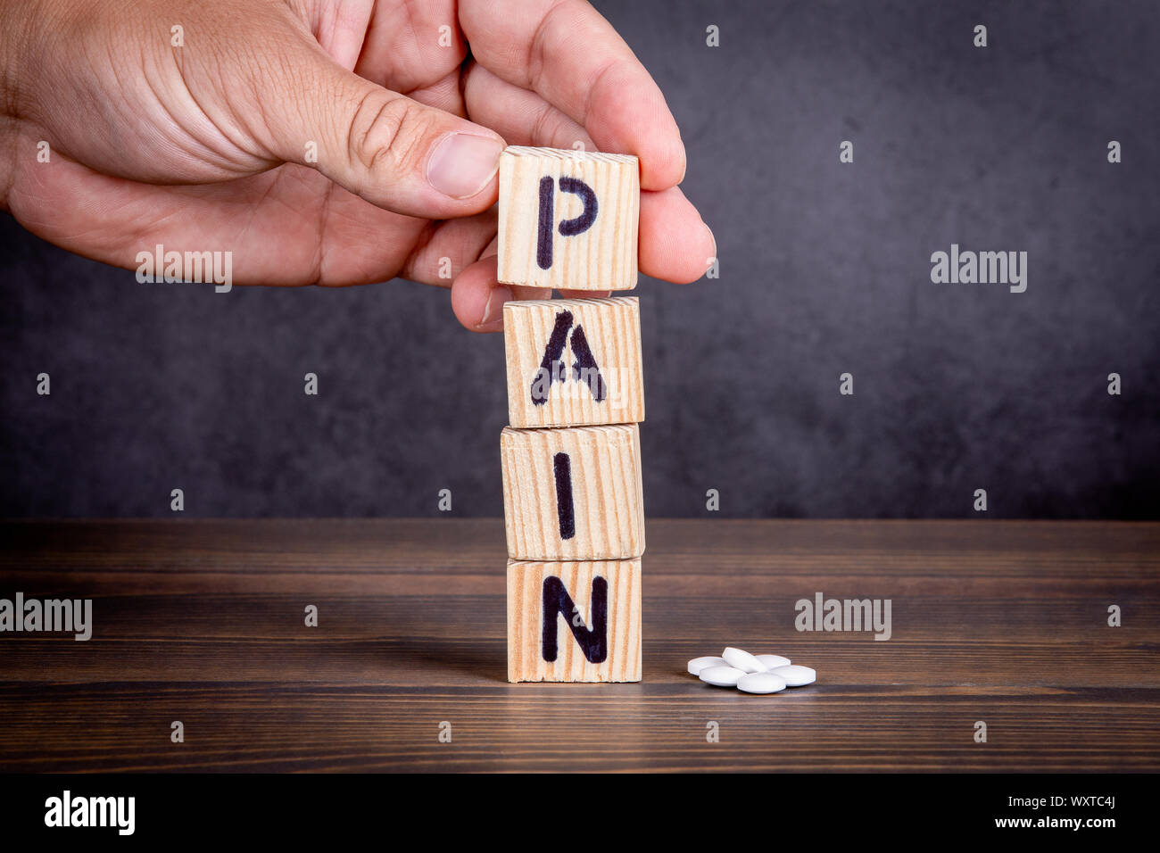 Concepto de dolor. Letras de madera y pastillas de color blanco Foto de stock