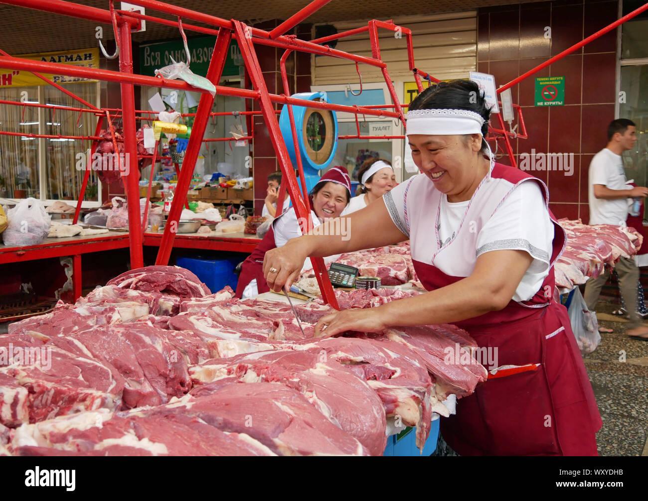 Almaty, Kazajstán - Agosto 24, 2019: sonrientes mujeres que trabajan en la sección de carne del famoso bazar verde en Almaty, Kazajstán Foto de stock