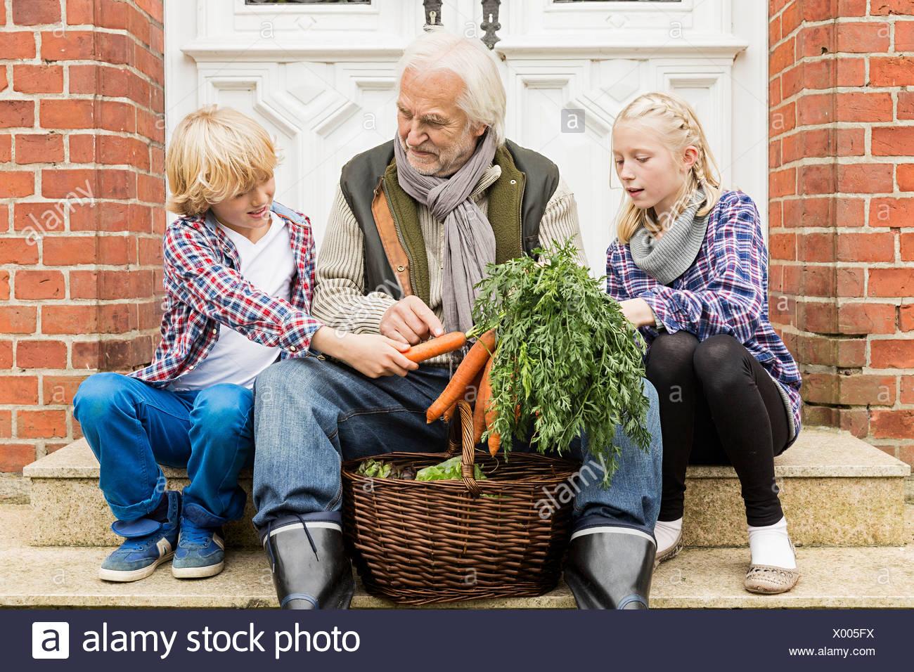Abuelo sentado con sus nietos en la puerta con zanahorias Imagen De Stock