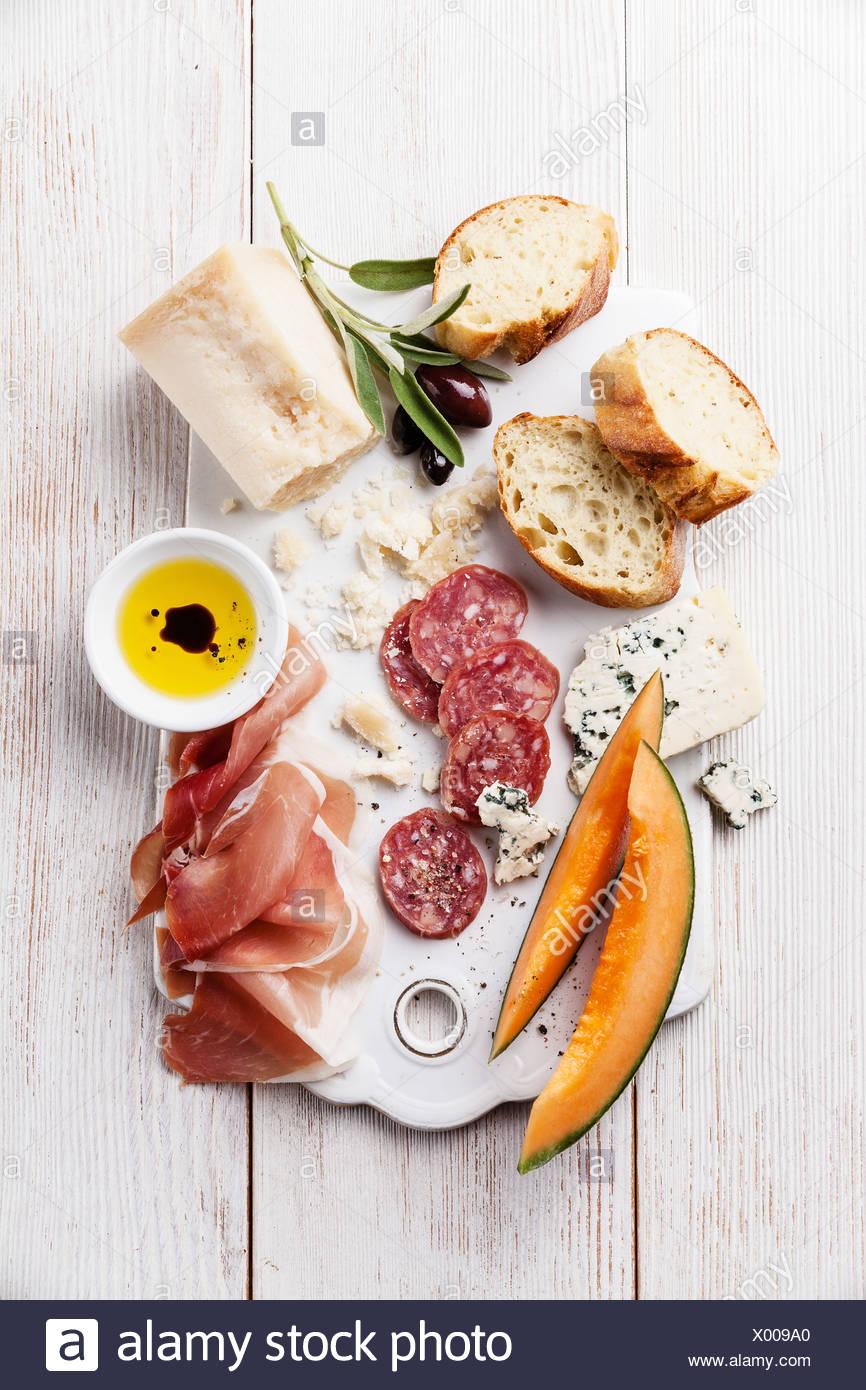Entremeses de jamón, queso, melón y aceite de oliva con aromas balsámicos Imagen De Stock