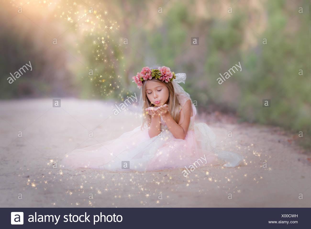 Chica sentada en la carretera, soplando glitter Imagen De Stock