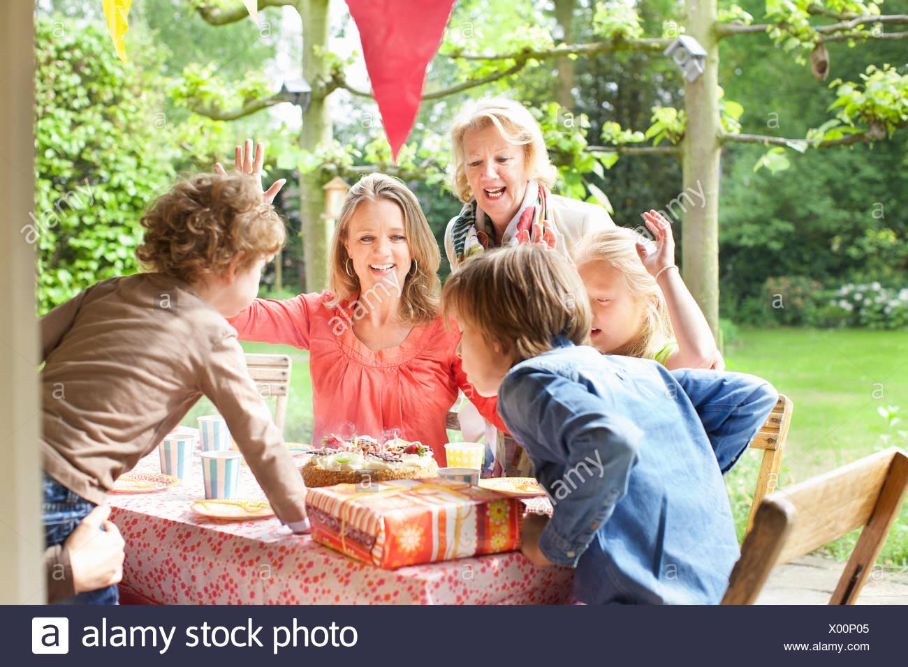 Familia cantando y vitoreando en fiesta de cumpleaños Imagen De Stock